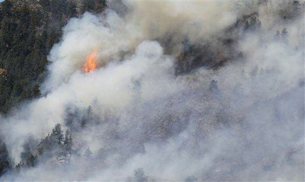 Fire burns through trees Monday on the High Park wildfire near Fort Collins, Colo. The wildfire is burning out of control in northern Colorado, while an unchecked blaze choked a small community in southern New Mexico as authorities in both regions battled fires Monday. Associated Press