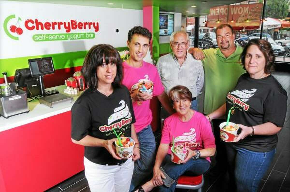Catherine Avalone - The Middletown Press Owners of CherryBerry Middletown, a self-serve yogurt bar, from left to right, Jodi and Peter Mendlinger, at left, Maria, seated and Bob Balaban, Johnny Moore and Elisa Balaban opened at 423 Main Street. The hours are 11 a.m. - 10:30 p.m.