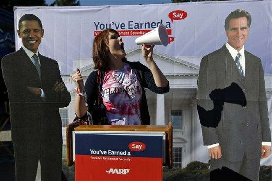 Hofstra University junior Corinne Mestemacher poses with life size cut out cardboards of President Obama and Republican presidential candidate, former Massachusetts Gov. Mitt Romney on campus ahead of the presidential debate, Tuesday, Oct. 16, 2012, in Hempstead, N.Y. President Obama and Republican presidential candidate, former Massachusetts Gov. Mitt Romney will hold their second debate on Tuesday night. (AP Photo/Mary Altaffer) Photo: AP / AP