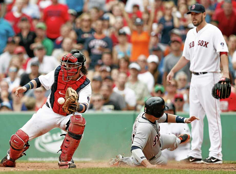 Detroit Tigers' Victor Martinez slides home safely on a triple by Andy Dirks while Boston Red Sox catcher Jarrod Saltalamacchia, left, takes the throw with starting pitcher John Lackey looking on during the seventh inning of Detroit's 3-0 win in a baseball game at Fenway Park in Boston, Monday, Sept. 2, 2013. (AP Photo/Winslow Townson) Photo: AP / FR170221 AP