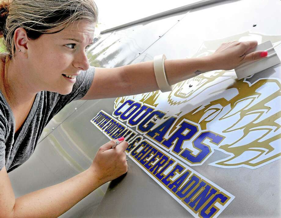 Kara Tarallo, assistant manager at Home Team Supply letters a trailer for Haddam-Killingworth Youth Football & Cheerleading Thursday afternoon on Sabrook Road in Middletown. Catherine Avalone - The Middletown Press Photo: Journal Register Co. / TheMiddletownPress