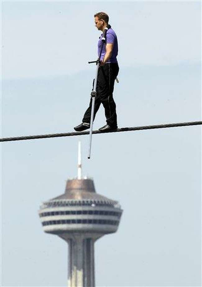 Nik Wallenda performs a walk on a tightrope with the Skylon Tower in the background during training in Niagara Falls, N.Y., Tuesday. Wallenda can't visit a new place without envisioning a wire strung high above his head: Linking buildings, landmarks, nations. Even as a 6-year-old at Niagara Falls with his parents, he pictured walking a tightrope over the raging, whitewater. Now 33, he's ready to live out that childhood fantasy when he attempts on Friday to become the first person ever to walk a tightrope directly over the brink of Niagara Falls.  Associated Press Photo: AP / AP