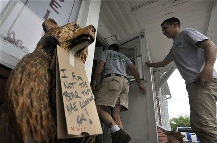 In this May 29 file photo, a sign hangs around the neck of a wooden bear at the entrance to the Old Village Store, in West Barnstable, Mass. A 200-pound black bear caught the imagination of Massachusetts residents as it meandered across Cape Cod before being relocated to central Massachusetts. Associated Press Photo: AP / Cape Cod Times