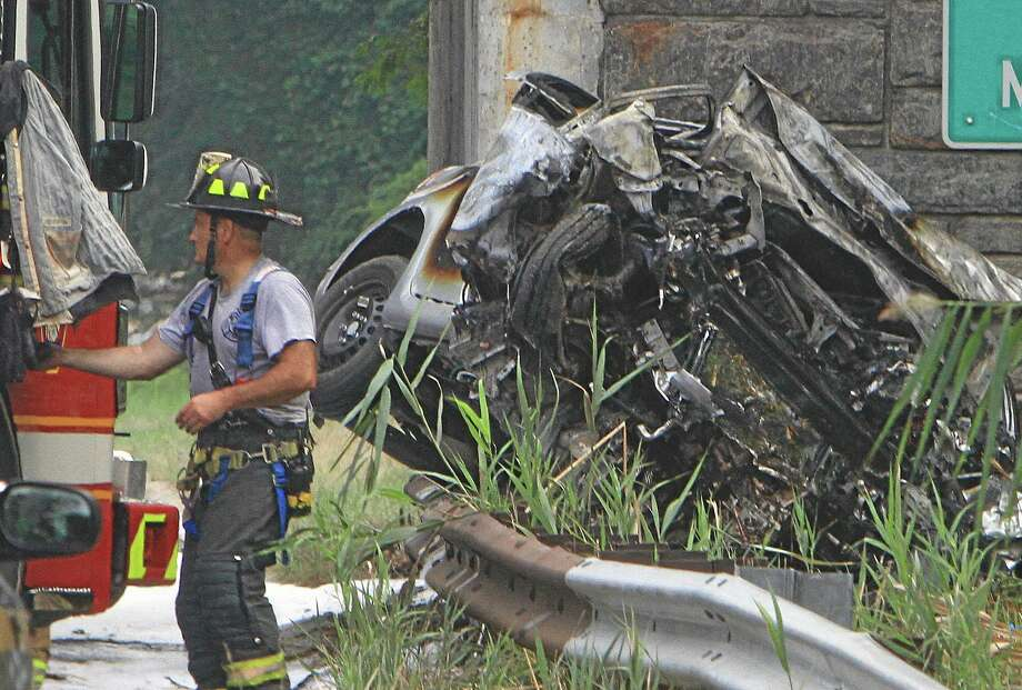Emergency personnel work at the scene of a multi-fatal accident on the northbound Sprain Brook Parkway in Greenbugh, N.Y. on Sunday, Sept. 1, 2013. Police said the car hit the Underhill Road Bridge and burst into flames killing all four occupants early Sunday morning. (AP Photo/The Journal News, Frank Becerra Jr.) Photo: AP / The Journal News