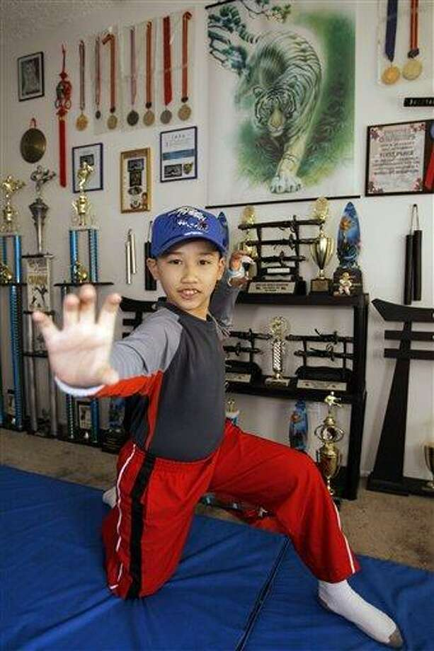 In this 2008 file photo, Moshe Kai Cavalin, 10, strikes a martial arts position as he poses for photos at his home studio in Downey, Calif. At age 11, Cavalin became the youngest person ever to earn an Associate in Arts degree from East Los Angeles College and now, at 14, is poised to graduate with honors from UCLA later this year. Associated Press Photo: AP / AP2008