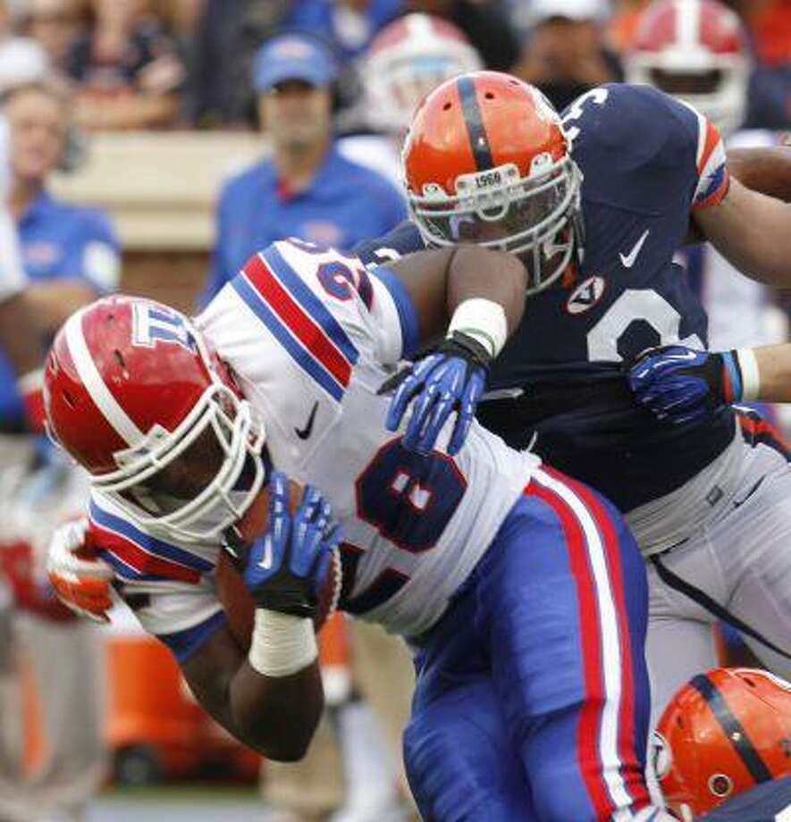 Louisiana Tech running back Kenneth Dixon (28) is stopped by Virginia defensive end Ausar Walcott (3) during the first half of an NCAA college football game at Scott Stadium in Charlottesville, Va., Saturday, Sept. 29, 2012. Photo: ASSOCIATED PRESS / AP2012
