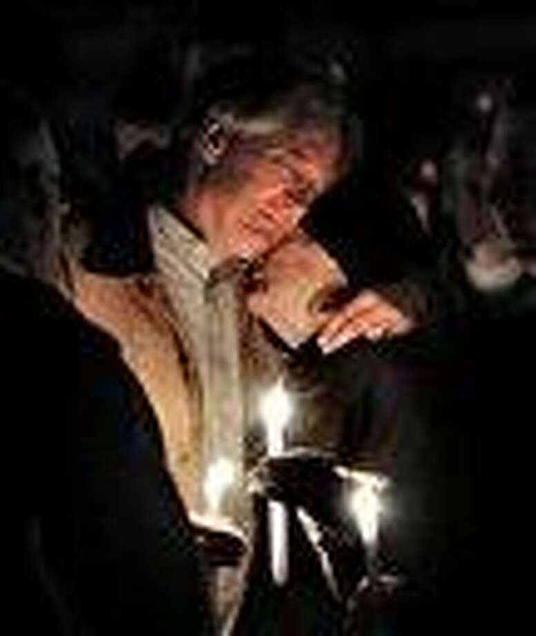 "Robert Marriott, father of Lizzi Marriott, is consoled during an emotional candlelight vigil at the Bay State Commons, for his daughter, Elizabeth ""Lizzi"" Marriott of Westboro, a University of New Hampshire student, who disappeared earlier in the week. Marriott is believed to be dead, and a man has been charged with second-degree murder. AP Photo Photo: AP / Telegram & Gazette"