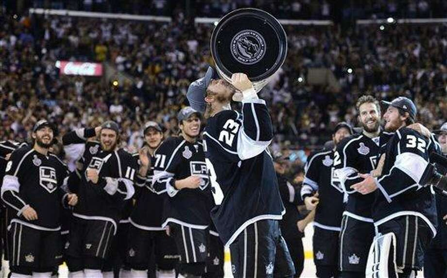 Los Angeles Kings captain Dustin Brown (23) kisses the Stanley Cup after the Kings defeated the New Jersey Devils 6-1 in Game 6 of the NHL hockey Stanley Cup finals, Monday, June 11, 2012, in Los Angeles. (AP Photo/Mark J. Terrill) Photo: AP / Copyright 2012 The Associated Press. All rights reserved. This material may not be published, broadcast, rewritten or redistributed.