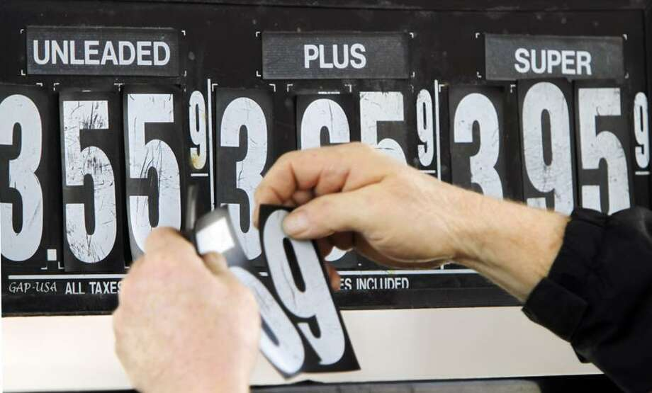 Gas station manager Fred Oliver, of Lisbon Falls,  Maine, changes the price of gasoline on the pumps at a station in Topsham, Maine.  Associated Press Photo: AP / AP2012