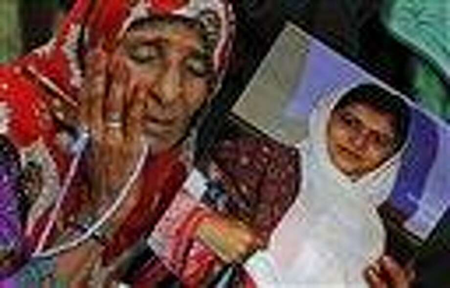 A supporter of Pakistani political party Muttahida Qaumi Movement (MQM), reacts while holding a poster of 14-year-old schoolgirl Malala Yousufzai, who was shot last Tuesday by the Taliban for speaking out in support of education for women. Tens of thousands rallied in Pakistan's largest city Sunday in support of the girl. AP Photo/Shakil Adil Photo: AP / AP