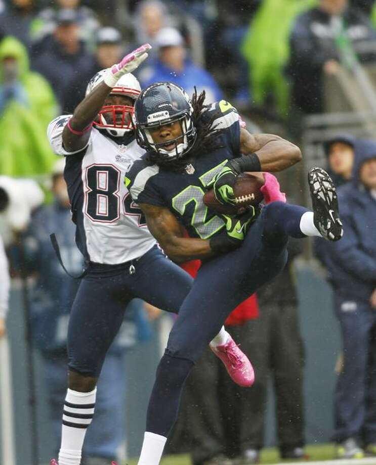 Seattle Seahawks' Richard Sherman (25) intercepts a pass intended for New England Patriots wide receiver Deion Branch (84) in the second half of an NFL football game, Sunday, Oct. 14, 2012, in Seattle. (AP Photo/John Froschauer) Photo: AP / AP2012