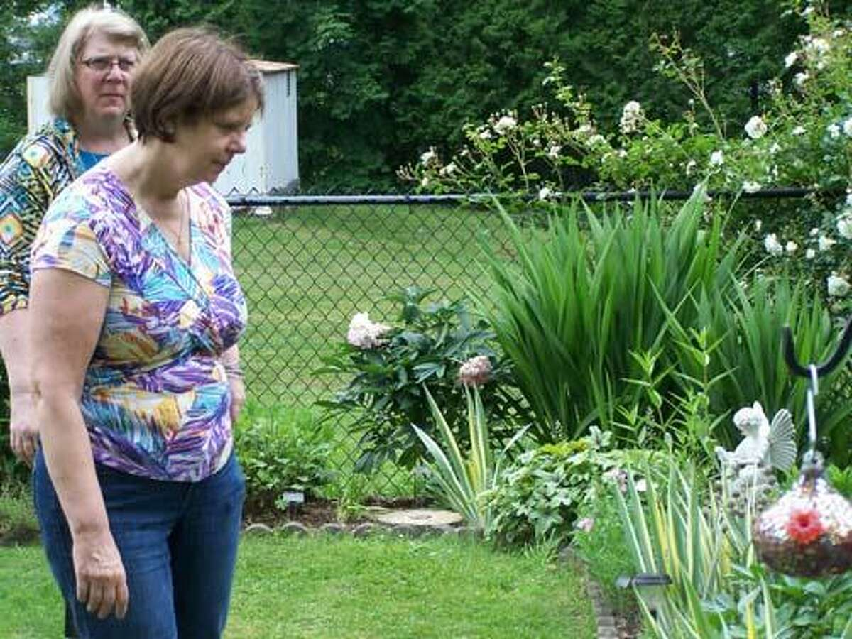 Kathy Lalikos and Barbara Dimberg of Chester look over a garden on Cherry Hill Road in Middlefield. The garden wa spart of a tour sponsored by the Middletown Garden Club Saturday