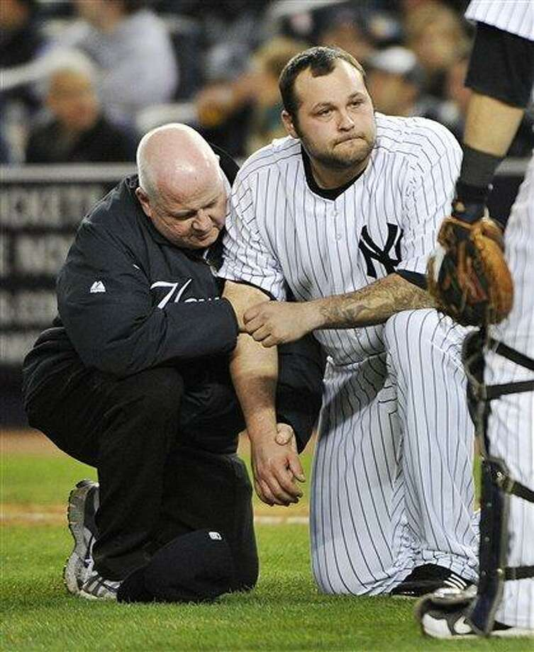 A trainer, left, helps New York Yankees relief pitcher Joba Chamberlain who was hit by a broken bat when Baltimore Orioles' Matt Wieters hit a single during the twelfth inning of Game 4 of the American League division baseball series on Thursday, Oct. 11, 2012, in New York. (AP Photo/Bill Kostroun) Photo: ASSOCIATED PRESS / AP2012