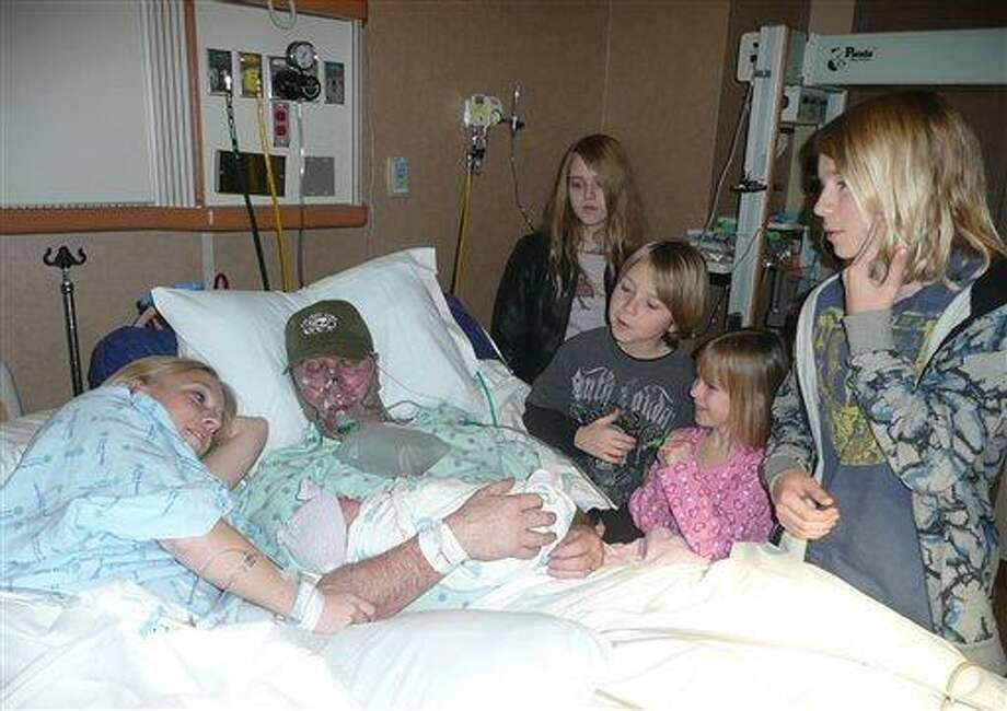 In this Jan. 18, 2012 photo provided by Diane Aulger, Diane, left, lies next to husband Mark Aulger, who holds their just-born daughter Savannah for the first time, at a hospital in Plano, Texas. The Aulger's other children stand at bedside, from back left to right: Lori, 15; Nicholas, 10; Ava, 7; and Trenton, 13. Associated Press Photo: AP / Diane Aulger