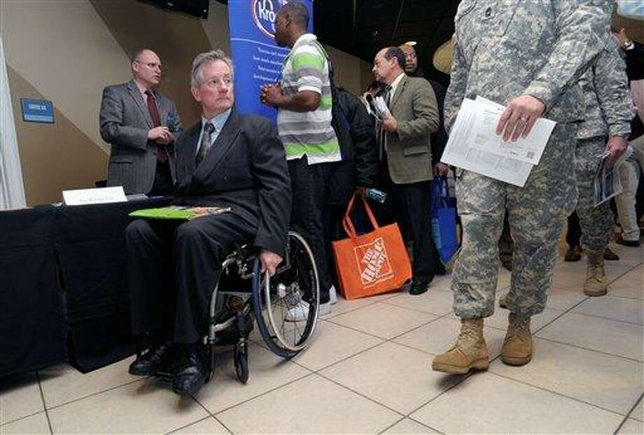 Disabled army veteran Ken Higgins, of Lilburn, Ga., finishes with a recruiter as he and other veterans attend a military-to-civilian job and education fair held Feb. 9 at Turner Field, in Atlanta. General Electric Co. plans to hire 5,000 veterans over the next five years and invest $580 million to expand its aviation business. Associated Press Photo: AP / FR69715 AP