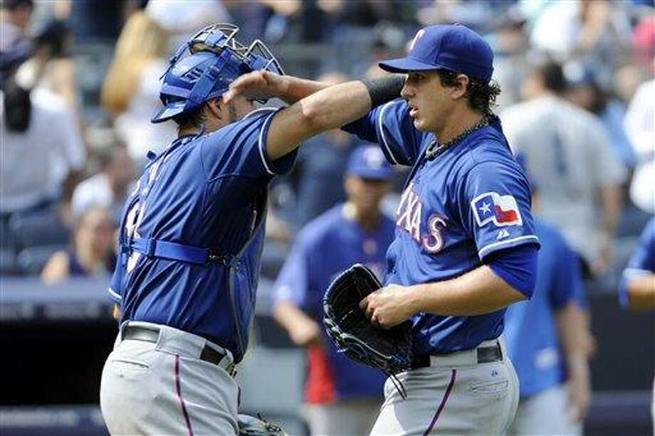 Texas Rangers catcher Geovany Soto, left, celebrates with pitcher Derek Holland after Holland pitched a complete game as the Rangers defeated the New York Yankees, 2-0, in a baseball game Thursday, June 27, 2013, at Yankee Stadium in New York. (AP Photo/Bill Kostroun) Photo: AP / FR51951 AP