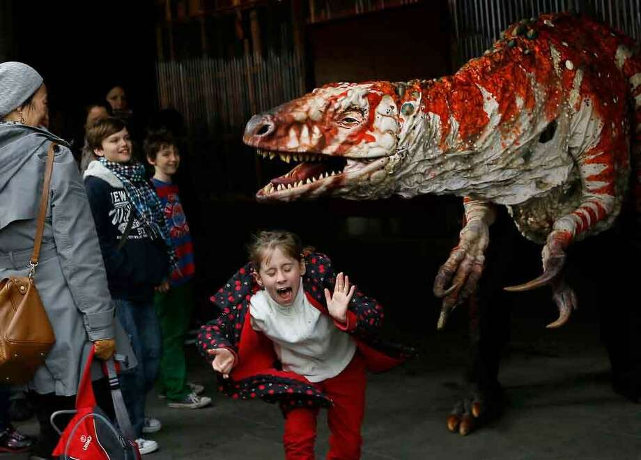 Children react as a carnivorous theropod known as the Australovenator dinosaur walks through crowds along the Southbank, in London, Monday, Feb. 18, 2013. The dinosaur is one of many that can be visited at the Erth's Dinosaur Petting Zoo, visiting from Australia, the creatures can be touched and fed at the Southbank Centre. (AP Photo/Kirsty Wigglesworth) Photo: ASSOCIATED PRESS / AP2013