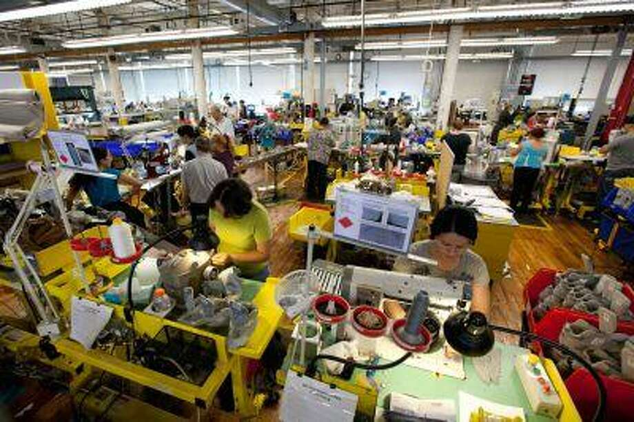 Workers assemble sneakers at the New Balance Athletic Shoe factory in Lawrence, Mass., in 2011. The House voted this month to require the Pentagon to give American-made athletic shoes to recruits, after more than three years of lobbying by New Balance. (Scott Eisen/Bloomberg)