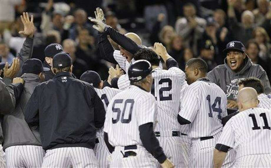 New York Yankees' Raul Ibanez celebrates with teammates as he reaches home plate after hitting the game-winning home run during the 12th inning of Game 3 of the American League division baseball series against the Baltimore Orioles on Wednesday, Oct. 10, 2012, in New York. The Yankees 3-2. (AP Photo/Kathy Willens) Photo: AP / AP