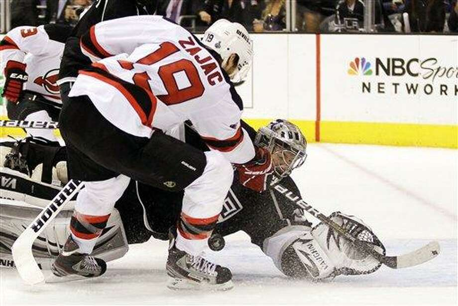 Los Angeles Kings goalie Jonathan Quick stops a shot on the goal by New Jersey Devils' Travis Zajac (19) in the third period during Game 4 of the NHL hockey Stanley Cup finals, Wednesday, June 6, 2012, in Los Angeles. The Devils won the game 3-1. (AP Photo/Julie Jacobson) Photo: AP / AP