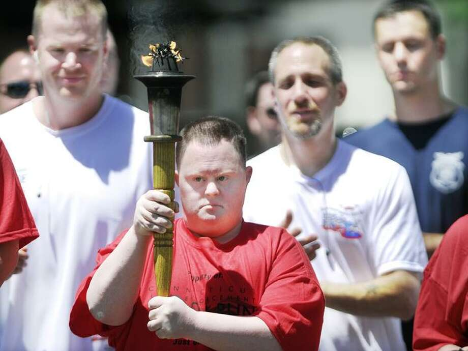 @CAvaloneMP  6.7.12   Special Olympian Scott Thayer, of Middletown carries the Torch of Hope running along side Detective Dan Petrulis and members of the Middletown Police Department on Broad Street in Middletown during the Connecticut Law Enforcement  Special Olympic Torch Run 2012.