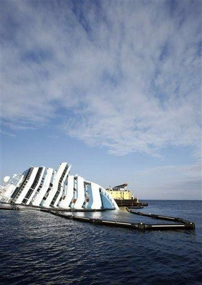 An anti-oil spilling barrier floats around the grounded cruise ship Costa Concordia off the Tuscan island of Giglio, Italy, this week. The Concordia ran aground on Jan. 13 after the captain deviated from his planned route and gashed the hull of the ship on a reef. The ship contains about 500,000 gallons (2,400 tons) of heavy fuel and other pollutants.  Associated Press Photo: AP / AP