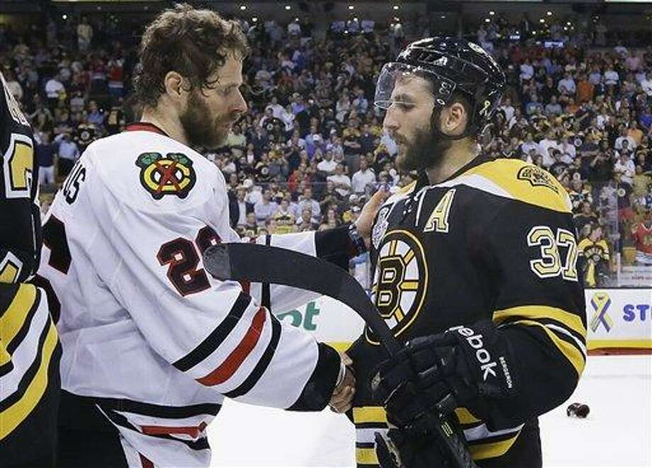 Chicago Blackhawks center Michal Handzus (26), of Slovakia, shakes hands with Boston Bruins center Patrice Bergeron (37) after the Blackhawks beat the Bruins 3-2 in Game 6 of the NHL hockey Stanley Cup Finals Monday, June 24, 2013, in Boston. (AP Photo/Elise Amendola) Photo: AP / AP