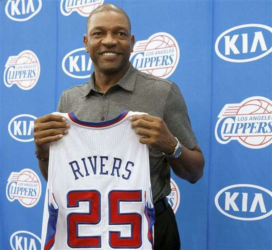 Former Boston Celtics head coach Doc Rivers holds his new Los Angeles Clippers jersey during a press conference in Los Angeles on Wednesday, June 26,  2013. Rivers was introduced as the Clippers' new coach and senior vice president of basketball operations.   (AP Photo/Nick Ut) Photo: AP / AP