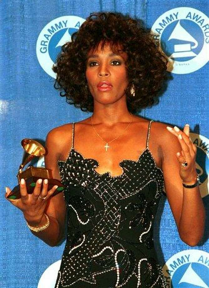 FILE - In this March 3, 1988, file photo, Whitney Houston poses with her Grammy at the annual Grammy Awards presentation in New York. Publicist Kristen Foster said, Saturday, Feb. 11, 2012, that singer Whitney Houston has died at age 48.    (AP Photo/Mark Lennihan, File) Photo: AP / AP1988