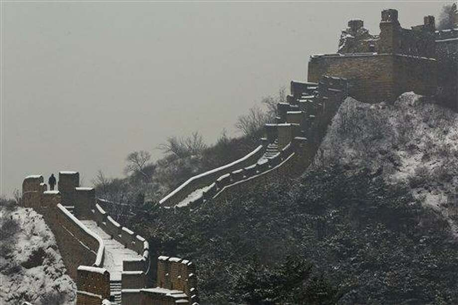 A tourist climbs part of the Great Wall after a snow in Luanping, in northern China's Hebei province, Friday, Dec. 14, 2012. (AP Photo/Alexander F. Yuan) Photo: AP / AP
