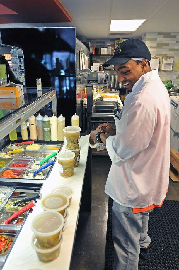 New Haven-- Terry Williams fills soups for customers at the new Elm City Market at 360 State Street. Williams, an ex-offender got the job at the city Re-Entry Roundtable job fair held in October.   Peter Casolino/New Haven Register02/07/12