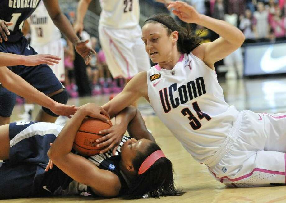ASSOCIATED PRESS Connecticut's Kelly Faris dives for a loose ball during Saturday's game against Georgetown at Gampel Pavilion in Storrs.