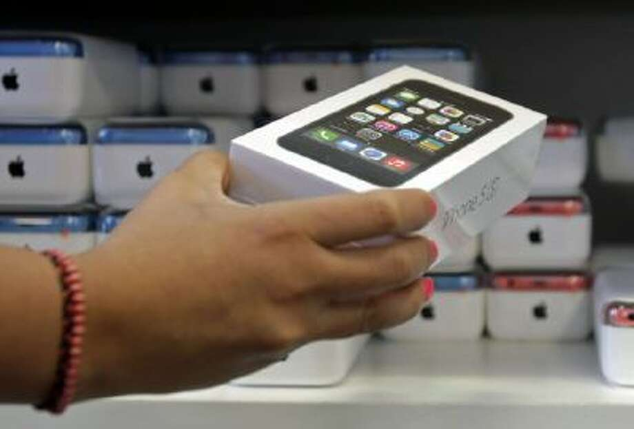 A sales person pulls out an iPhone 5s for a customer during the opening day of sales of the iPhone 5s and iPhone 5C, in Hialeah, Fla., Monday, Sept. 23, 2013.
