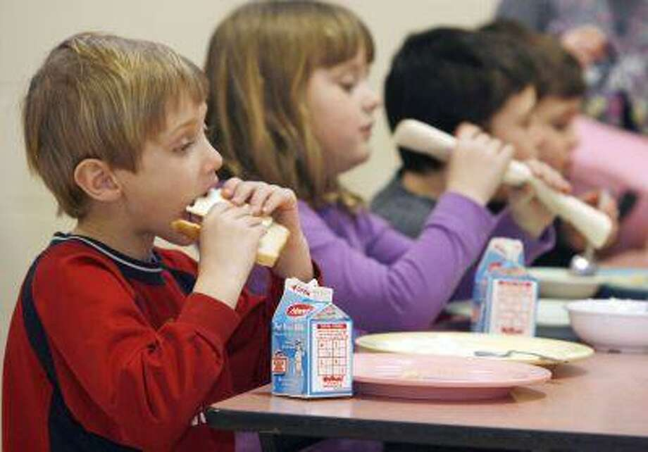 In this Feb. 3, 2010 file photo, students eat lunch at Sharon Elementary School in Sharon, Vt. Vermont ranks second in the country in an annual report of kids' well-being. The Annie E. Casey Foundation's Kids Count report released Monday shows improvements in eight areas like in the percentage of children with health insurance and fewer teen births but poverty continues to be a problem. Vermont fell slightly in the percentage of children with parents who lack secure employment to 29 percent. New Hampshire was the top-ranked state, followed by Vermont and Massachusetts. Nevada, Mississippi and New Mexico took the bottom three spots. Overall, Vermont ranked third in the country in education and family and community and fourth in health. (AP Photo/Toby Talbot) Photo: ASSOCIATED PRESS / AP2010