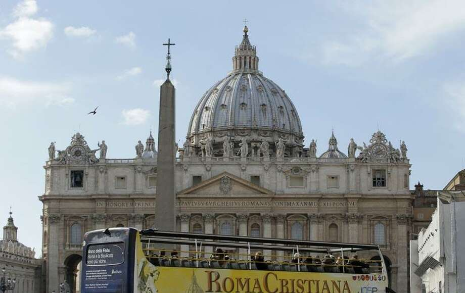 "A tourist bus that reads ""Christian Rome"" drives past Saint Peter's Basilica at the Vatican February 13, 2013. Cardinals around the world began informal contacts to discuss who should next lead the Church through a period of major crisis and the Vatican said it planned a big send-off for Pope Benedict before he becomes the first pontiff in centuries to resign. REUTERS/Max Rossi Photo: REUTERS / X90039"