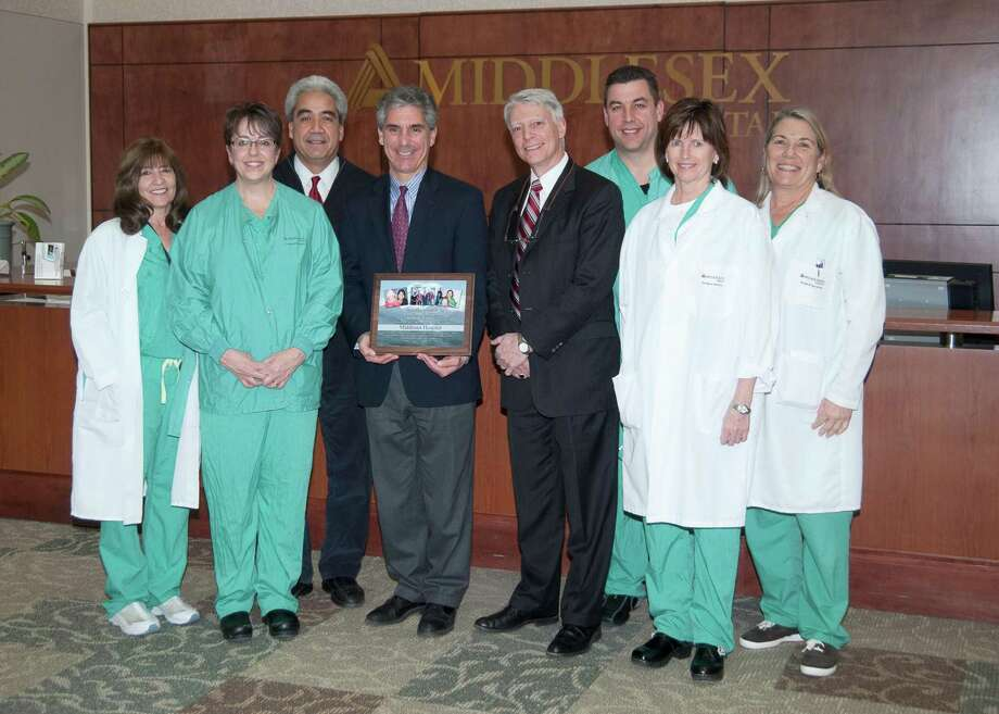 (in center, left to right) Vincent G. Capece, President/CEO of Middlesex Hospital and Paul Martel, founder of the Clinica Dulce Refugio. They are surrounded by several members of the surgical team, including (left to right) Anne Gowac, R.N., Denise Levy, R.N., Jonathan Blancaflor, M.D., David Jagrosse, Beth Delaney, R.N., and Barbara Thompson, R.N. (Photo by John Giammatteo) Photo: John Giammatteo / ©John Giammatteo 2012