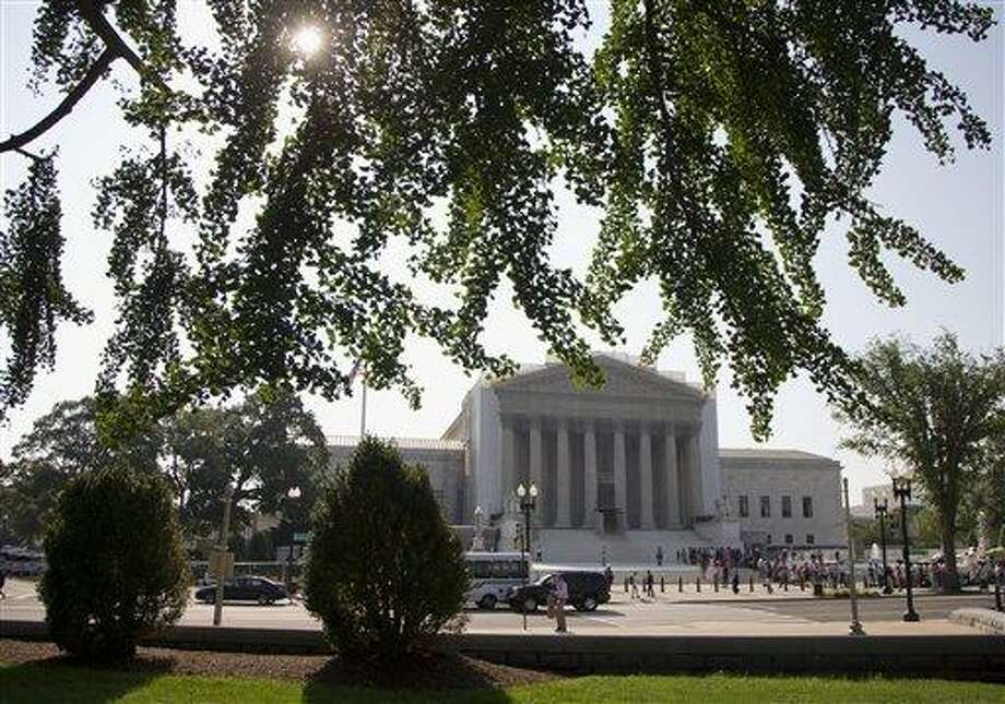 People wait in line outside the Supreme Court in Washington, Monday, June 24, 2013, as key decisions are expected to be announced. The Supreme Court has 11 cases, including the term's highest profile matters, to resolve before the justices take off for summer vacations, teaching assignments and international travel. The court is meeting Monday for its last scheduled session, but will add days until all the cases are disposed of.  (AP Photo/Carolyn Kaster) Photo: AP / AP