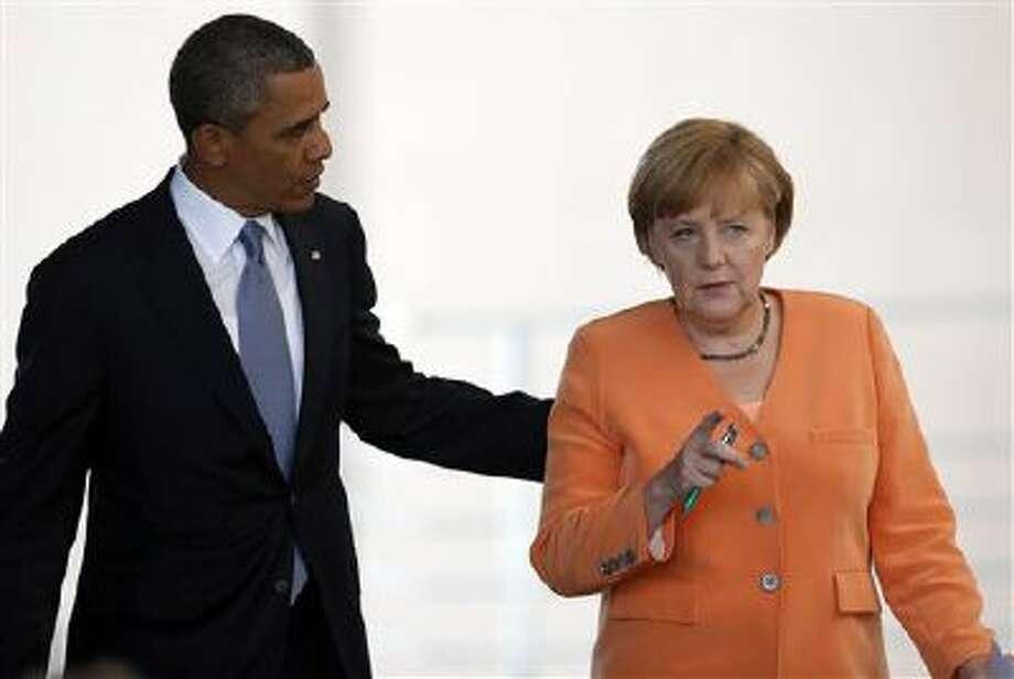 President Barack Obama, left, and German Chancellor Angela Merkel, right, talk after addressing media on June 19. Photo: AP / AP