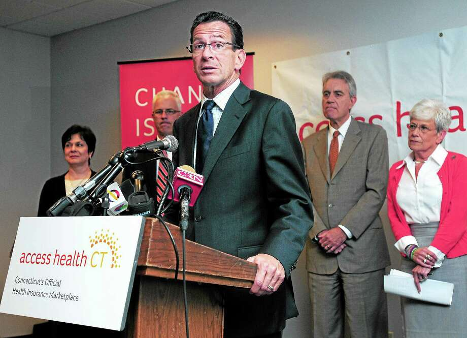 (Arnold Gold — New Haven Register)  Governor Dannel Malloy speaks about the Affordable Care Act on the first day of open enrollment at the Access Health CT call center in Hartford on 10/1/2013.  At right is Kevin Counihan, CEO of Access Health CT, and at far right is Lt. Governor Nancy Wyman. Photo: Journal Register Co.