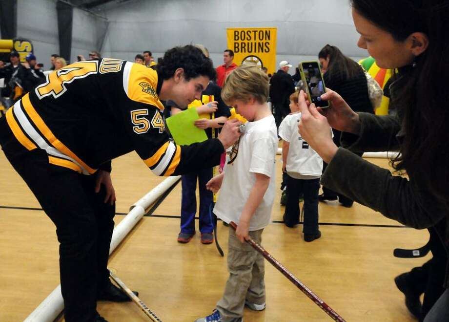 The Boston Bruins made a visit to the Newtown Youth Academy signing autographs and playing street hockey for town residents only. Adam McQuaid signs seven-year-old Logan Johnson's t-shirt while his mom takes a photo. Mara Lavitt/New Haven Register2/18/13