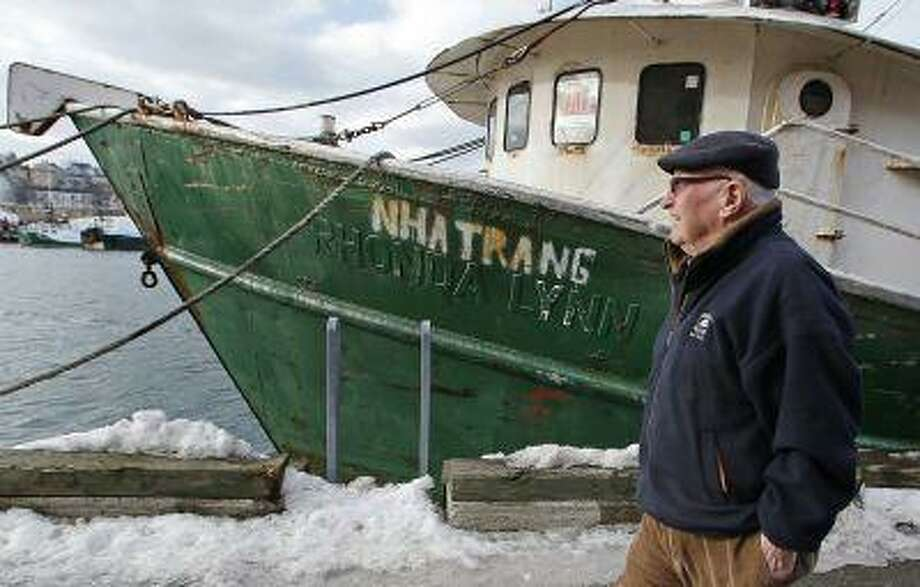 In this photo taken Wednesday, Feb. 13, 2013, Ron Gilson, a 79-year-old life Gloucester native, walks along the fish pier in Gloucester, Mass. In Gilson's life he's worked throughout the fishing industry from working on the wharf in his youth to a historian on Gloucester in his later life. In May, a massive reduction is coming to the catch limit for cod caught in the Gulf of Maine, just outside Gloucester Harbor, and the cuts are acknowledged by fishermen, regulators and environmentalists to be devastating, and perhaps fatal, for the historic industry. (AP Photo/Charles Krupa) Photo: AP / AP