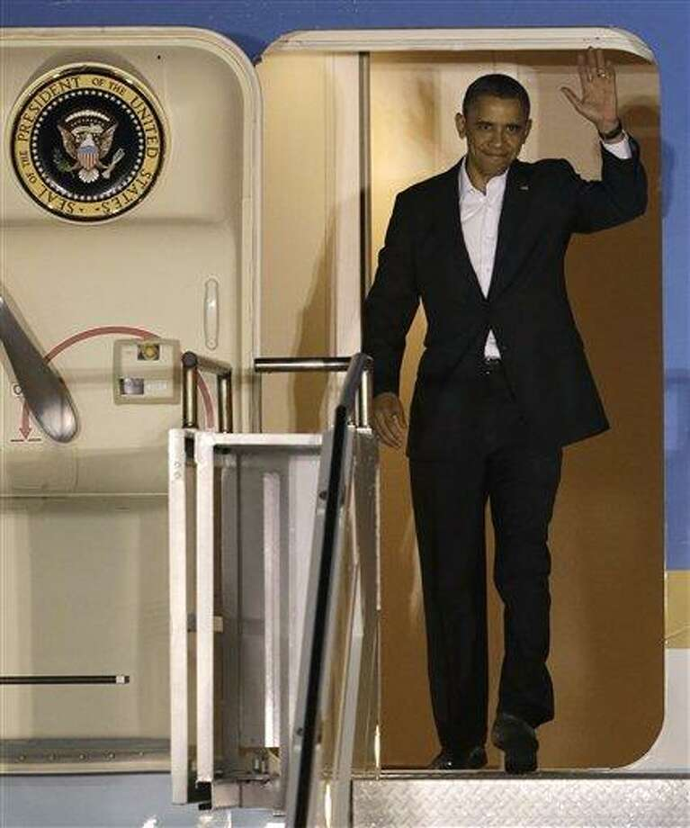 President Barack Obama waves as he walks down the stairs of Air Force One upon his arrival at Palm Beach International Airport, Friday, Feb. 15, 2013 in West Palm Beach, Fla. (AP Photo/Wilfredo Lee) Photo: AP / AP