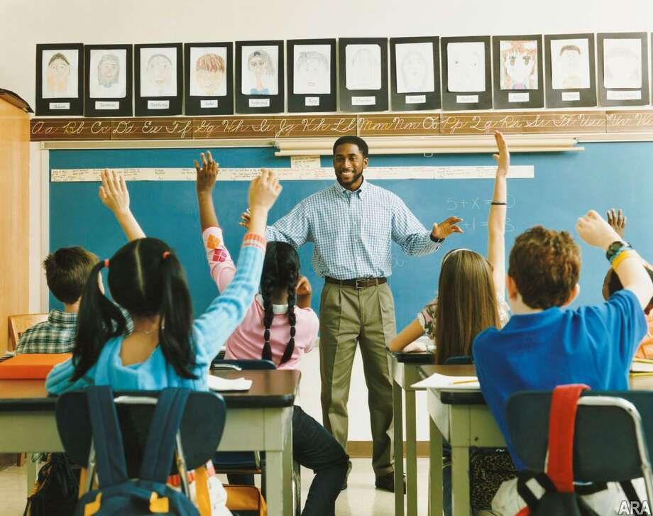 Teacher Standing in Front of a Class of Raised Hands Photo: Getty Images/Digital Vision / Digital Vision