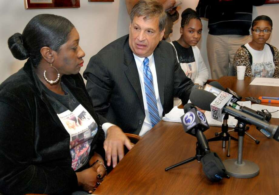 Attorney Richard Altschuler turns to comfort Olemae Hardy, left, mother of Chauncey Hardy, after he spoke some graphic details of her son's death. In back are Chauncey Hardy's sisters Jada Kinsey, left, 15, and Onnalise Hardy, 19. Altschuler held a press conference top discuss new details in the case.    Melanie Stengel/Register