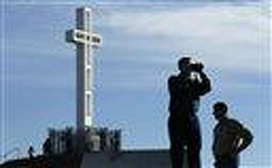 In this 2011 file photo, Rev. John Fredericksen of Orlando, Fla.,  alongside Burdette Streeter of San Diego, takes a picture in front of the war memorial cross on Mount Soledad in San Diego. Supporters of the war memorial, which is on public land in San Diego, are planning to ask the Supreme Court to reverse a federal court's decision deeming the cross unconstitutional.  Associated Press Photo: AP / AP2011