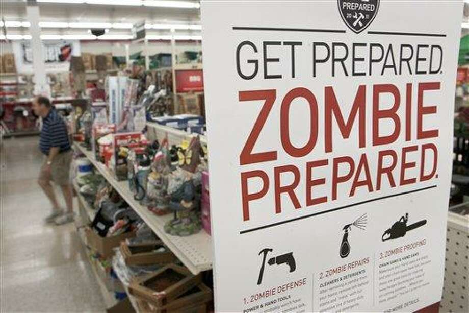 In this October 2011 file photo, a sign promoting zombie preparedness displays in a hardware store in Omaha, Neb. After several gory incidents that have been reported around the country recently, online zombie talk has grown. Associated Press Photo: AP