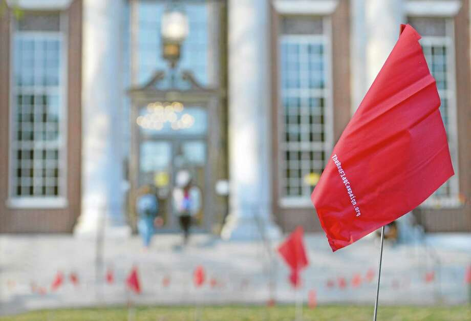 Hundreds of little red flags wave in the breeze in front of Olin Library at Wesleyan University, representing those who have been sexually harassed. Photo: Brittany Hill - Middletown Press Intern
