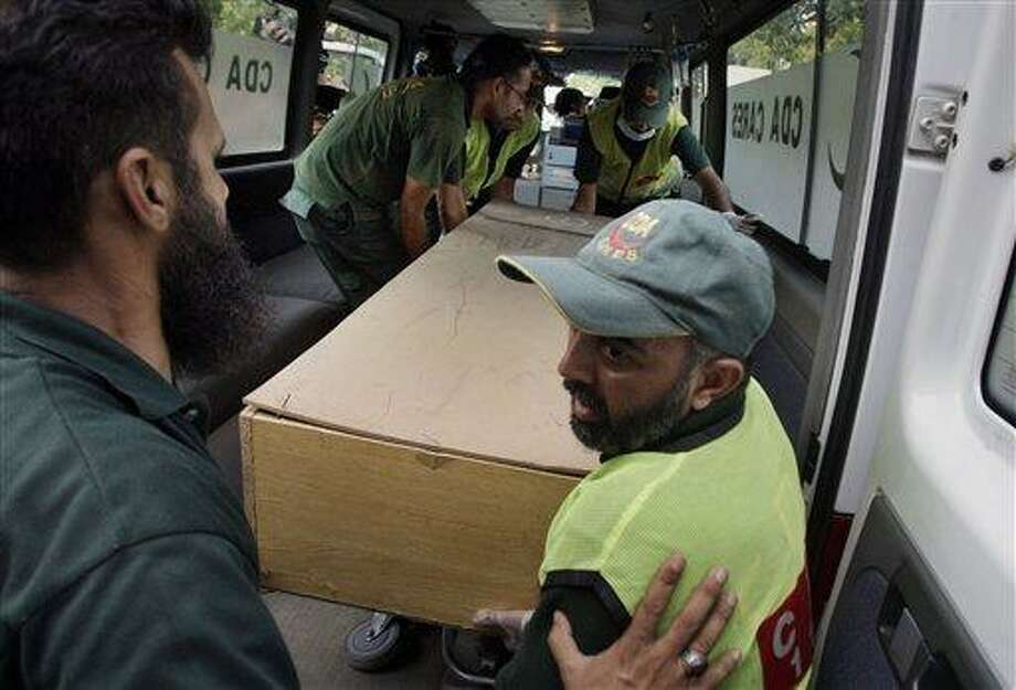Pakistani rescue workers unload the casket of a foreign tourist, who was killed by Islamic militants, from an ambulance to shift in a morgue of local hospital in Islamabad, Pakistan, Sunday, June 23, 2013. Islamic militants wearing police uniforms shot to death nine foreign tourists and one Pakistani before dawn as they were visiting one of the world's highest mountains in a remote area of northern Pakistan that has been largely peaceful, officials said. (AP Photo/Anjum Naveed) Photo: AP / AP