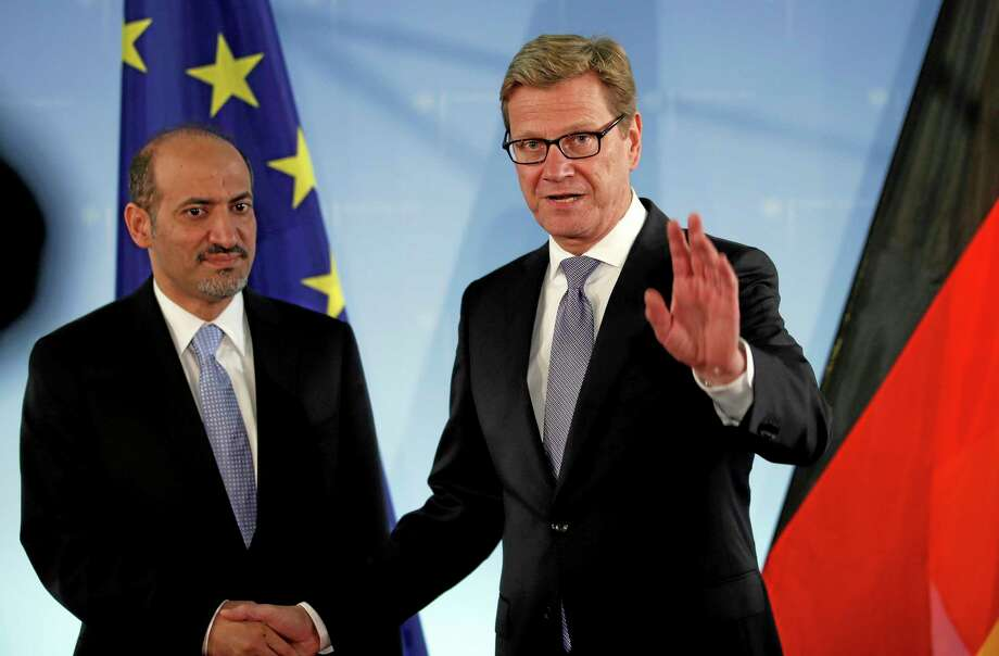FILE - In this Sept. 2, 2013 file photo, German Foreign Minister Guido Westerwelle, right, and the chairman of the national coalition of the Syrian opposition, Ahmad Jarba, left, shake hands for the media prior to a meeting at the Foreign Ministry in Berlin, Germany. The main Western-backed Syrian opposition group is facing intense pressure from the United States and its European allies to attend a long-delayed peace conference aimed at ending Syria's civil war, a move that holds the potential to cause an irreparable split in the opposition in exile. (AP Photo/Michael Sohn, File) Photo: AP / AP
