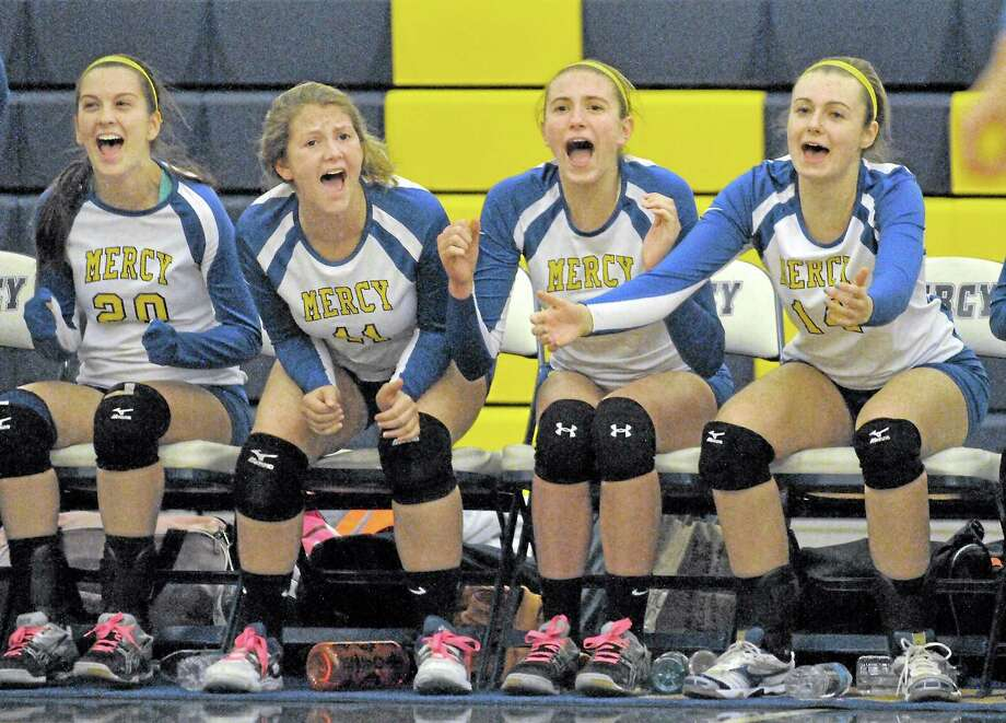 Members of the Mercy volleyball team, left to right, Caralyn Cianciolo, Madeline Kumm, Janella Spada and Mackenzie Dugan celebrate after the Tigers defeat Lyman Hall 3-1 Monday night. Photo: Catherine Avalone — The Middletown Press  / TheMiddletownPress